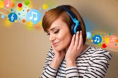 Mujer joven que escucha la música con los auriculares Fotos de archivo