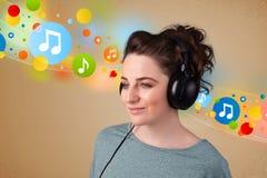 Mujer joven que escucha la música con los auriculares Foto de archivo