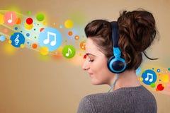 Mujer joven que escucha la música con los auriculares Imagenes de archivo