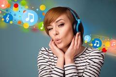 Mujer joven que escucha la música con los auriculares Imágenes de archivo libres de regalías