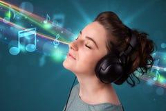 Mujer joven que escucha la música con los auriculares Fotos de archivo libres de regalías