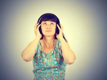 Mujer joven que escucha la música con los auriculares Imagen de archivo libre de regalías