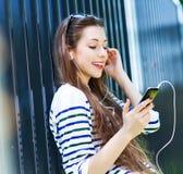 Mujer joven que escucha la música con smartphone Foto de archivo