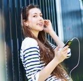 Mujer joven que escucha la música con smartphone Fotos de archivo