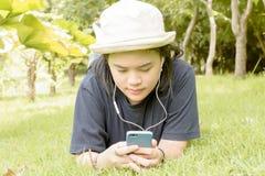 Mujer joven que escucha la música de su teléfono elegante en los gras Fotografía de archivo
