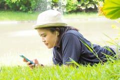 Mujer joven que escucha la música de su teléfono elegante en los gras Foto de archivo