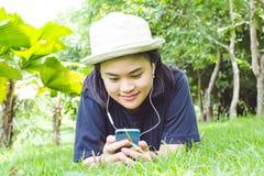 Mujer joven que escucha la música de su teléfono elegante en los gras Fotos de archivo libres de regalías
