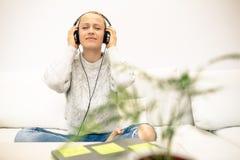 Mujer joven que escucha la música del teléfono elegante usando los auriculares imágenes de archivo libres de regalías