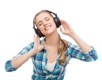 Mujer joven que escucha la música en auriculares Fotos de archivo libres de regalías