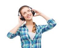Mujer joven que escucha la música en auriculares Fotos de archivo