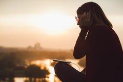 Mujer joven que escucha la música en el smartphone Imagenes de archivo