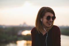 Mujer joven que escucha la música en el smartphone Fotos de archivo libres de regalías