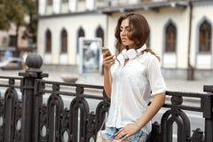 Mujer joven que escucha la música en los auriculares Imágenes de archivo libres de regalías