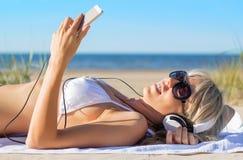 Mujer joven que escucha la música en los auriculares Fotografía de archivo
