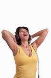 Mujer joven que escucha la música en los auriculares que disfrutan de una danza en el fondo blanco Fotos de archivo
