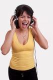 Mujer joven que escucha la música en los auriculares que disfrutan de una danza en el fondo blanco Fotografía de archivo
