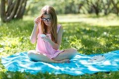 Mujer joven que escucha la música en los auriculares Se sienta en la hierba en el parque, descansando disfruta de la naturaleza fotografía de archivo