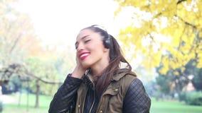 Mujer joven que escucha la música en los auriculares y el baile almacen de metraje de vídeo