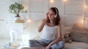 Mujer joven que escucha la música melodiosa en auriculares por mañana en dormitorio almacen de video