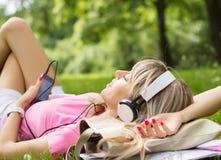 Mujer joven que escucha la música mientras que coloca en hierba Imagenes de archivo