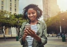 Mujer joven que escucha la m?sica de un tel?fono elegante fotografía de archivo libre de regalías