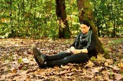 Mujer joven que escucha la música en naturaleza Imagen de archivo
