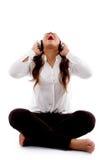 Mujer joven que escucha la música y que canta Fotos de archivo libres de regalías