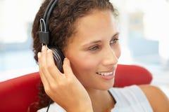 Mujer joven que escucha los auriculares imagen de archivo