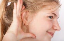 Mujer joven que escucha un ruido reservado Fotos de archivo