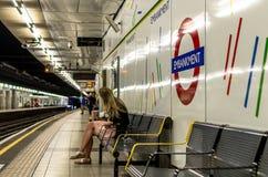 Mujer joven que espera el tubo en la estación del terraplén, Londres Fotos de archivo libres de regalías
