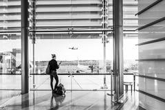 Mujer joven que espera en el aeropuerto, mirando a través de la ventana de la puerta Imagen de archivo