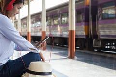 Mujer joven que espera en la plataforma de la estación con la mochila en tra Fotos de archivo