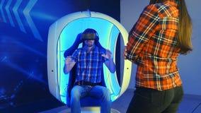 Mujer joven que espera su vuelta para la atracción de la realidad virtual Fotos de archivo