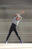 Mujer joven que estira ejercicio al aire libre Fotografía de archivo libre de regalías