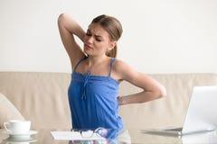 Mujer joven que estira el sufrimiento del dolor de espalda súbito, sintiendo Imagen de archivo libre de regalías