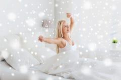 Mujer joven que estira en cama después de despertar Fotos de archivo libres de regalías