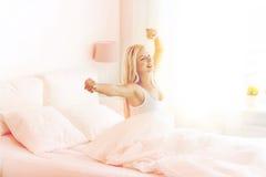 Mujer joven que estira en cama después de despertar Imagen de archivo
