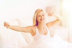 Mujer joven que estira en cama después de despertar Imágenes de archivo libres de regalías