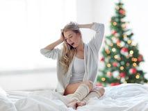 Mujer joven que estira en cama en la Navidad Fotografía de archivo