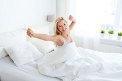 Mujer joven que estira en dormitorio de la cama en casa Imagenes de archivo