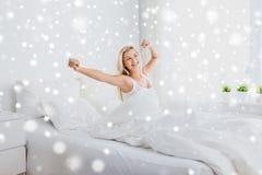 Mujer joven que estira en dormitorio de la cama en casa Imagen de archivo libre de regalías