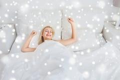 Mujer joven que estira en dormitorio de la cama en casa Imagen de archivo