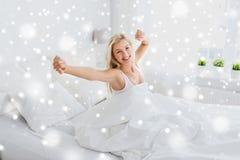 Mujer joven que estira en dormitorio de la cama en casa Fotos de archivo libres de regalías