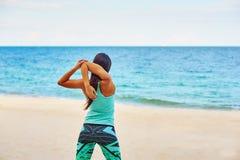 Mujer joven que estira en la playa Fotografía de archivo libre de regalías