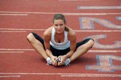 Mujer joven que estira en pista Fotografía de archivo libre de regalías