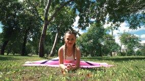 Mujer joven que estira en un parque Mujer atractiva joven de la aptitud que realiza una guita Concepto sano de la forma de vida almacen de video