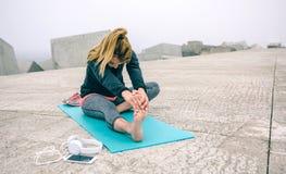 Mujer joven que estira las piernas por el embarcadero del mar Fotografía de archivo libre de regalías