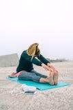 Mujer joven que estira las piernas por el embarcadero del mar Imagen de archivo
