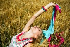 Mujer joven que estira para arriba en un campo del verano Imagen de archivo libre de regalías