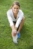 Mujer joven que estira sus piernas Fotos de archivo